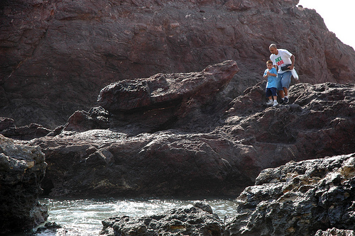 A man encouraging his son to walk on rocks, Mex Sabe t-shirt, carrying a tackle box, South Mazatlan, Mexico