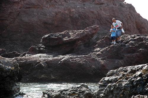 A man encouraging his son to walk on rocks, Mex Sabe t-shirt, carrying a tackle box, South Mazatlan, Mexico